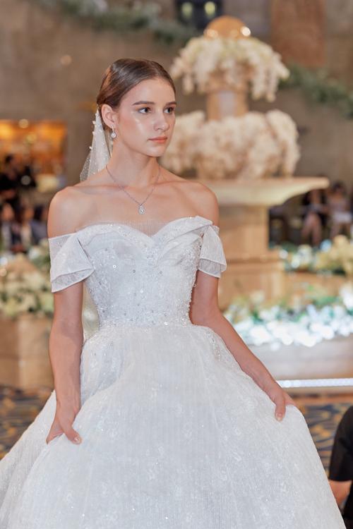 Mẫu đầm cổ tim được may thêm lớp vải mỏng, mang đến vẻ gợi cảm nhưng vẫn giữ cho váy cưới có sự duyên dáng, phù hợp văn hóa Á Đông. Trên thân váy là hạt cườm, đá lấp lánh.