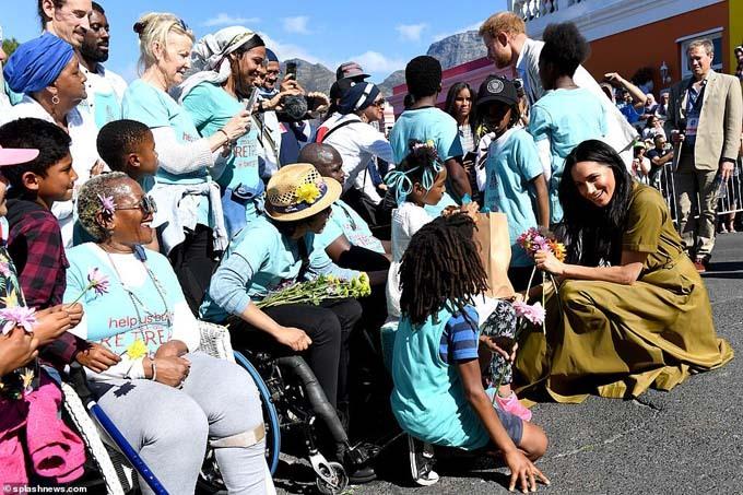 Meghan ngồi hẳn xuống để trò chuyện với trẻ em và nhóm người lớn tuổi đang chờ đợi để được gặp cô. Ảnh: Splashnews.