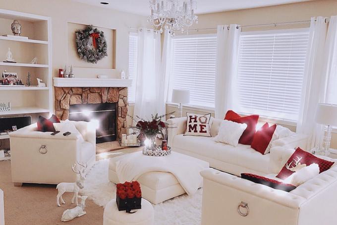 Phòng khách được trang trí chủ yếu là màu trắng, từ ghế sofa, rèm cửa đến tủ sách.