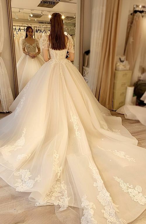 Cô dâu có thể chọn một chiếc váy đuôi dài với những bông renđiểm xuyếtvừa đủ để vẫn giữ được nét thanh thoát của vóc dáng và đúng với tinh thần giản lược của thời trang đương đại.