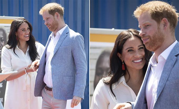 Hoàng tử Harry diễn tả biểu cảm hài hước trước khi được vợ dắt tay lên sân khấu phát biểu.
