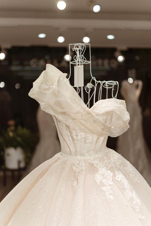 Sau cùng, chiếc váy được tạo ra với ý tưởng chính từ vẻ đẹp của bông hoa Calla nở rộ. Bởi loài hoa này là biểu tượng cho sắc đẹp lộng lẫy và gắn với ý nghĩa sự trở về của hạnh phúc nên phía sau những đường kim, mũi chỉ, NTK đã giúp cô dâu truyền tải mong ước về sự vẹn tròn, viên mãn.