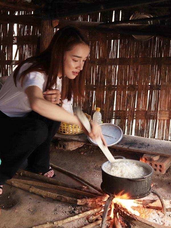 Cô nấu cơm bằng bếp củi và cẩn thận đảo lúc cơm sôi để tránh bị khê.