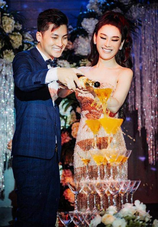 Vợ chồng ca sĩ chuyển giới tay trong tay rót rượu, thực hiện các nghi thức như ở tiệc cưới.