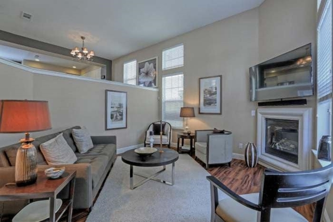 Kiến trúc ngôi nhà đi theo phong cách hiện đại với tông màu chủ đạo là màu xám. Phòng khách lót sàn gỗ và trang trí nhiều tranh ảnh.