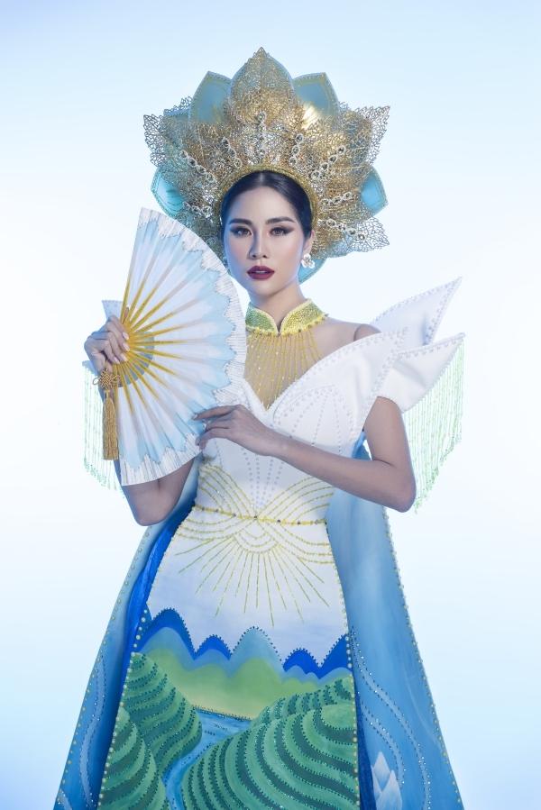 Phần áo choàng được xử lý in nổi, tạo hình hoa sen 3Dtăng thêmấn tượng. Người đẹp kết hợp mấn đội đầu tạo hình hoa sen, giúptrang phục hội tụ cả yếu tố truyền thống, hiện đại.