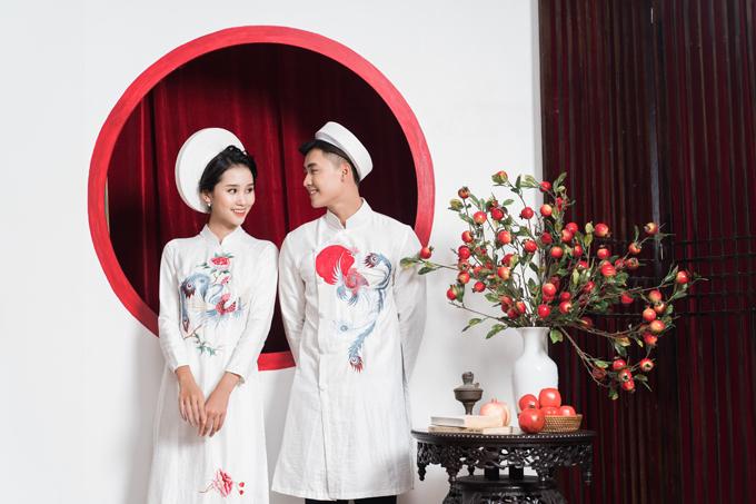 Tà áo dài đôi thể hiện sự đồng điệu, tình cảm gắn kết của lứa đôi thông qua màu sắc, họa tiết tương đồng. Mẫu áo nữ giữ nét truyền thống với cổ trụ, dáng áo đơn giản. Tuy nhiên, tấm áo được tạo sự mới mẻ với vạt áo ngắn hơn, phù hợp nhịp sống của cô dâu hiện đại.
