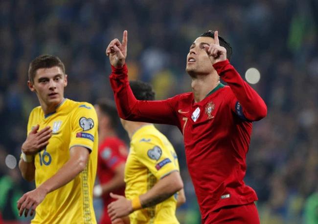 C. Ronaldo giơ hai ngón tay lên trời sau khi lập công ở chấm 11m trong trận thua 1-2 trước Ukraine