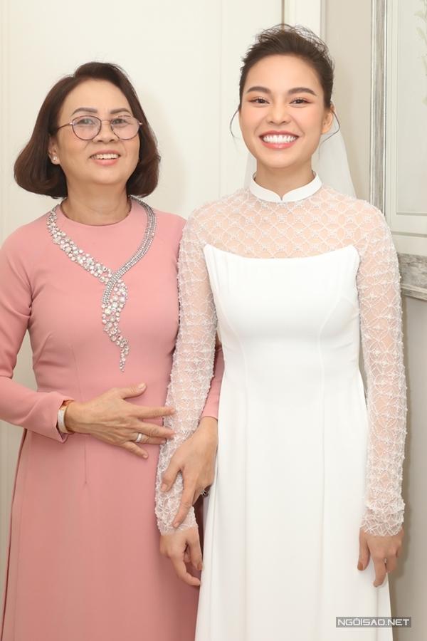 Giang Hồng Ngọc diện trang phục áo dài, được mẹ ruột nắm tay ra chào nhà trai.