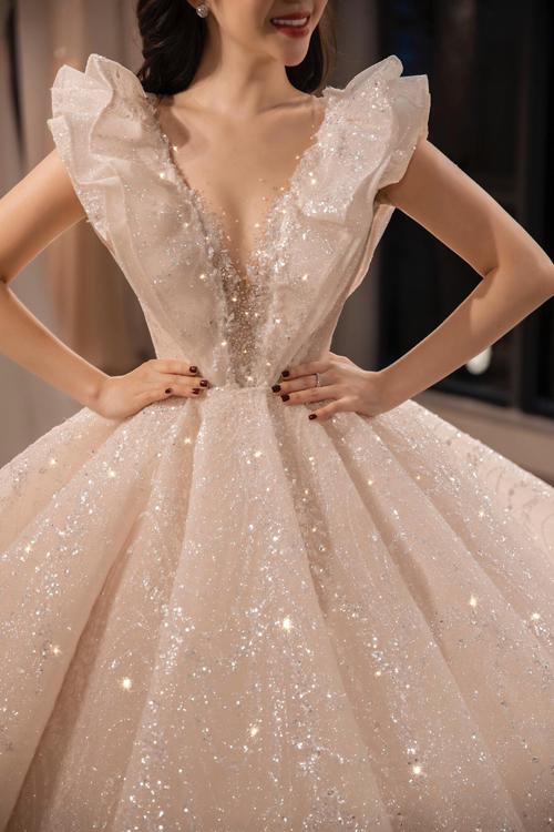 Váy mở cổ chữ V gợi cảm nhưng vẫn vẹn nguyên nét thanh lịch, sang trọng nhờ kiểu cổillusion neckline (cổ áo hư ảo).