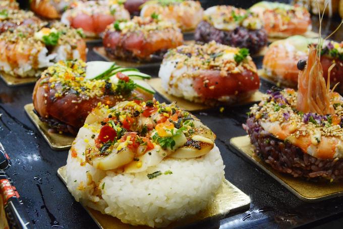 Không chỉ bán đồ ăn thô, những người bán hàng ở chợ cá Sydney rất biết cách làm thực khách mê mẩn bởi những biến tấu ấm thực ít nơi nào có được. Một trong những món được nhiều travel blogger quảng cáo nhất chính là món donut sushi với hình dáng giống một chiếc bánh donut với cơm trắng hoặc cơm gạo nâu, trộn dấm, nén chặt. Phần topping được trang trí sáng tạo, đầy màu sắc với các loại hải sản và phụ kiện mà chỉ cần lướt qua cũng khó mà rời mắt.
