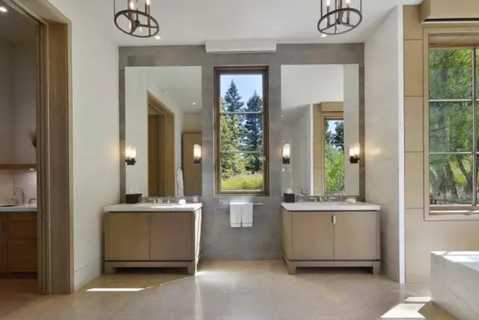 Trong phòng tắm còn được tích hợp thêm khu vực bàn trang điểm với điểm nhấn là những chiếc đèn vàng hình ngọn đuốt.