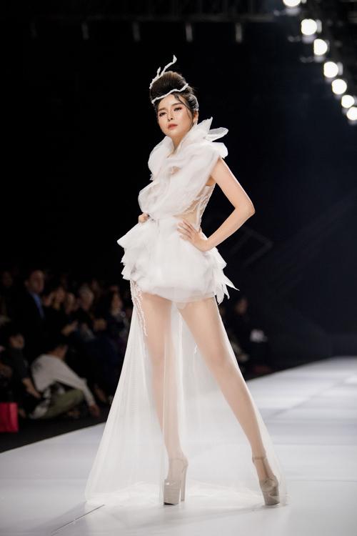 Người đẹp diện thiết kế jumpsuit phá cách với vải tulle xếp nếp bố cục tự do. Các dải dây leo điểm xuyết dọc thân, mang đến vẻ nữ tính, giúp thiết kế cân bằng được sự cá tính vốn có. Phần chân váy voan nhẹ nhàng giúp từng bước đi thêm uyển chuyển, thướt tha.