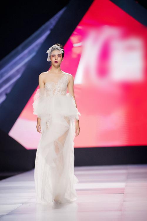 Váy có kết cấu vai bất đối xứng, phom dáng gọn gàng. Điểm nhấn được xếp đặt tinh tế, tránh sự quá đà.