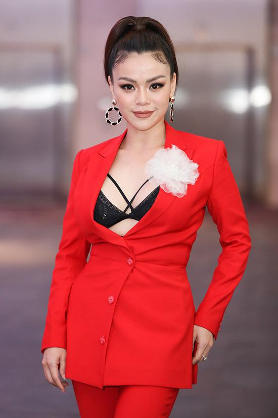 Nữ ca sĩ táo bạo khoe nội y với vest đỏ rực, xẻ cổ sâu. Cô rất hào hứng khi được mời làm giám khảo chương trình tìm kiếm các tài năng âm nhạc mới.