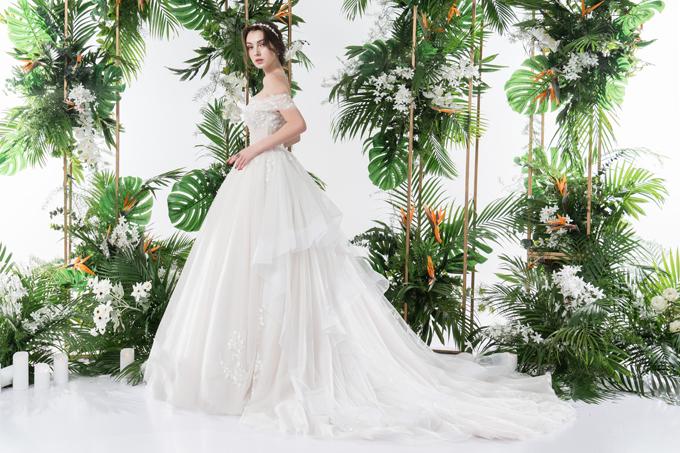 Váy trở thành dáng xòe nhờ tùng, có đuôi váy theo cấu trúc tầng bậc, tạo điểm níu giữ ánh nhìn, tăng nét cá tính cho người diện.