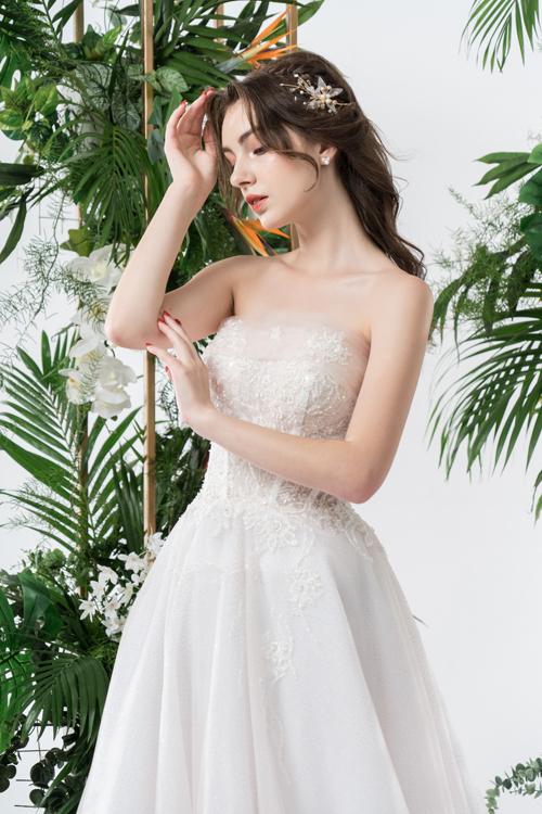 Bộ cánh cúp ngực giúp cô dâu khoe nét tươi trẻ nơi bờ vai thon, cần cổ gầy và xương quai xanh mảnh mai.