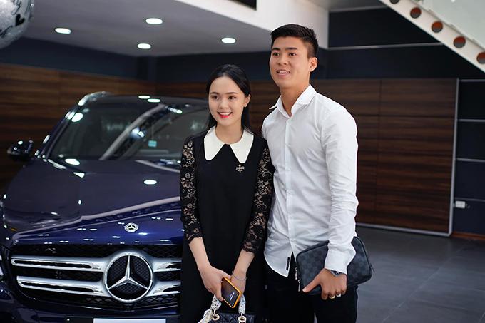 Duy Mạnh và Quỳnh Anh chụp ảnh bên chiếc xe mới mua.