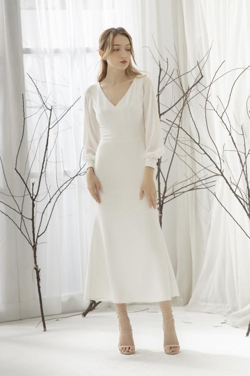 Kể từ đám cưới của Meghan Markle tháng 5/2019, váy tối giản trở thành hot hit của mùa cưới. Mẫu đầm có cổ xẻ chữ V, tay dài và độ dài tới giữa cẳng chân, giúp nàng dâu dễ di chuyển.