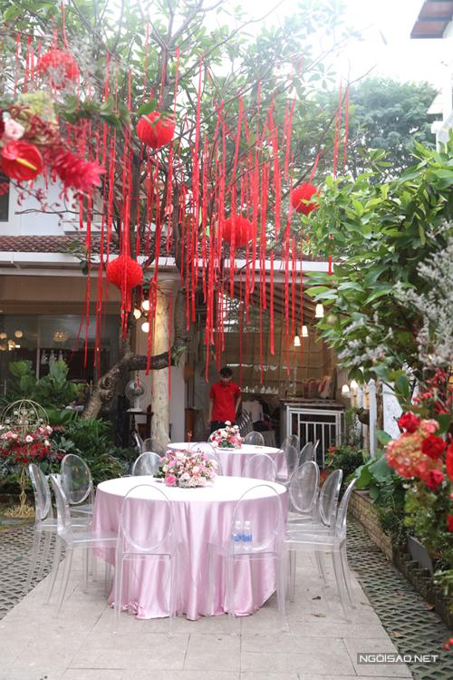 Chú rể chọn lựa ghế tàng hình (ghost chair) cho bàn trà tại lễ thành hôn. Bàn tròn phủ khăn trải bàn màu hồng tạo sự nhất quán cho bảng màu của không gian.