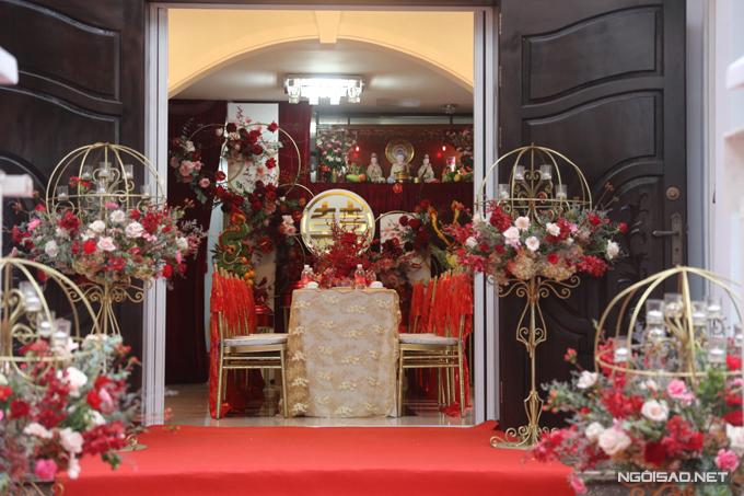Phía trong căn nhà mang tông màu chủ đạo là đỏ, vàng đồng, mang đến sự sang trọng. Chú rể chọn lựa bàn trà hình chữ nhật, ghế Chiavari gắn thêm dải lụa đỏ.
