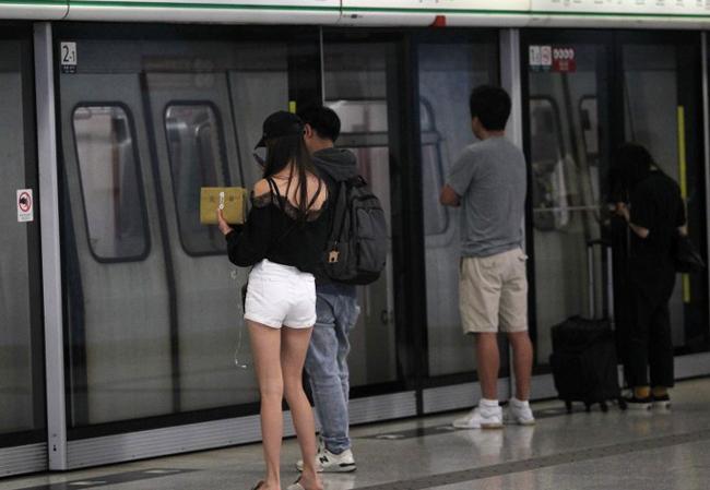 Chân dài Hong Kong xếp hàng chờ MTRcùng nhiều người khác. Trong khi chờ tàu, cô tranh thủ đọc sách.
