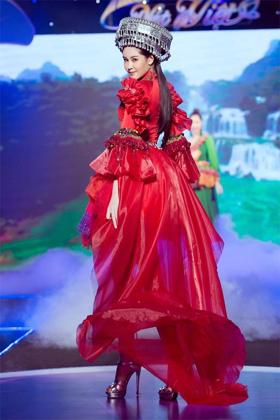 [Caption] Lê Âu Ngân Anh tham gia trình diễn cả hai bộ siêu tập của 2 NTK Việt Hùng và Thạch Linh. BST của NTK Việt Hùng mang đặc trưng của miền Tây sông nước còn của NTK Thạch Linh tái hiện lại bức tranh đầy màu sắc của dân tộc Tây Bắc.