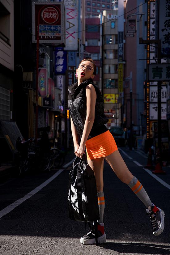Nữ ca sĩ chọn chiếc váy bó sát thân với màu cam nổi bật, những chi tiết màu sặc sỡ khác cũng được cônhấn nhá trong outfit này.
