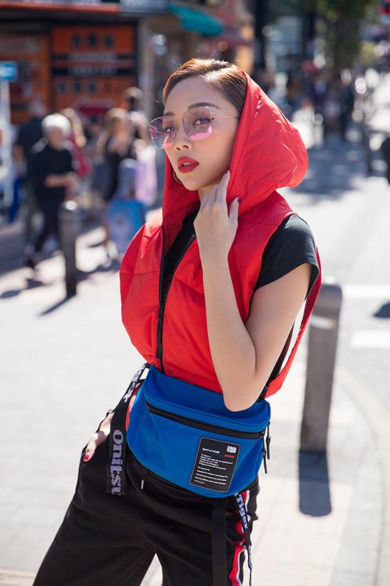 Chỉ với áo thun đen đơn giản cùng chiếc quần sọc dài thể thao, Tóc Tiênkhéo léo mix với áo khoác kéo khoá không tay đỏ bên ngoài làm bộ đồ nổi bật.