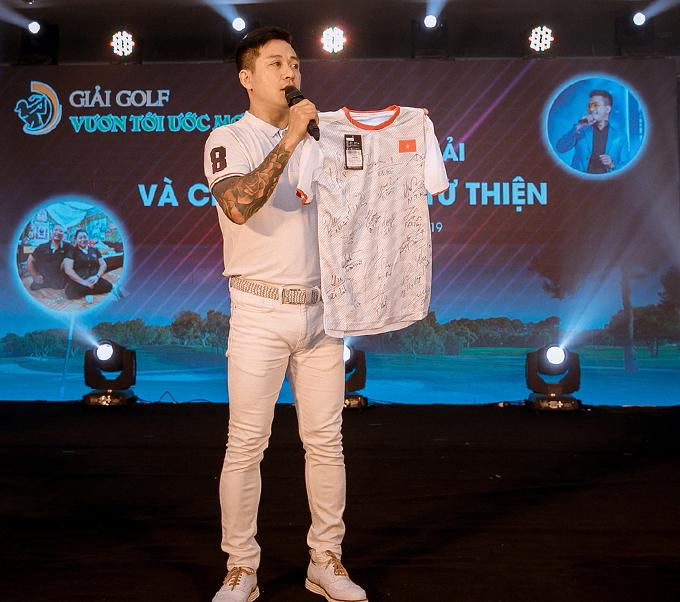 Tuấn Hưng đấu giá chiếc áo có chữ ký của các tuyển thủ Việt Nam trong đêmgala của giải golf Vươn tới ước mơ.