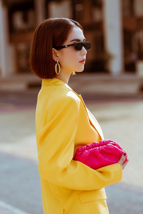 Blazer dáng rộng tông màu vàng tươi được mix cùng biker short. Ngọc Trình hoàn thiện set đồ dạo phố bằng mẫu clutch hồng cánh sen của Bottega Veneta.