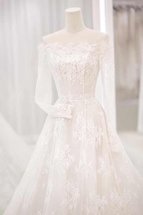 Ở mẫu đầm này, Chung Thanh Phong tiếp tục khai thác chất liệu ren tinh xảo. Tùng váy được thêu tay họa tiết hoa tỉ mỉ.