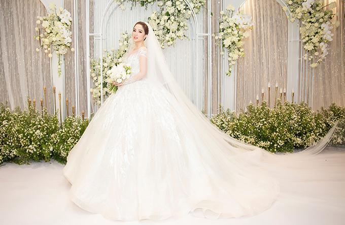 Đầm cưới chính của Bảo Thy được thiết kế giúp nàng dâu hóa thân thành nàng công chúa cổ tích. Bộ cánh dài tay có hiệu ứng bắt sáng từ mặt trước và mặt sau. Tùng váy bồng xòe, có đuôi dài khoảng 2 m, kiểu dáng corset siết eo.