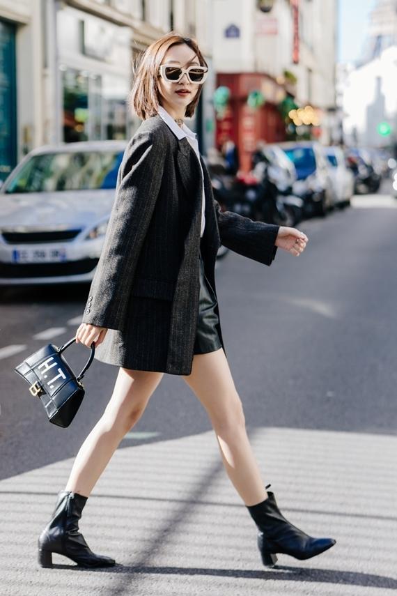 Áo sơ mi phối váy ngắn chữ A và áo blazer khoác ngoài là gợi ý thích hợp cho các bạn gái yêu thích phong cách trẻ trung, năng động. Túi xách in chữ H.T từ nhà mốt Balenciaga có giá khoảng 40 triệu đồng nhấn nhá cho tổng thể.