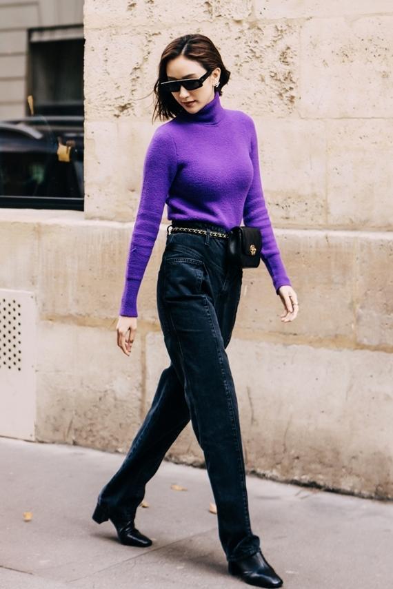 Bắt kịp xu hướng phối đồ màu nổi, Hà Thu chọn áo len cổ lọ màu tím mix cùng quần nhung đen.