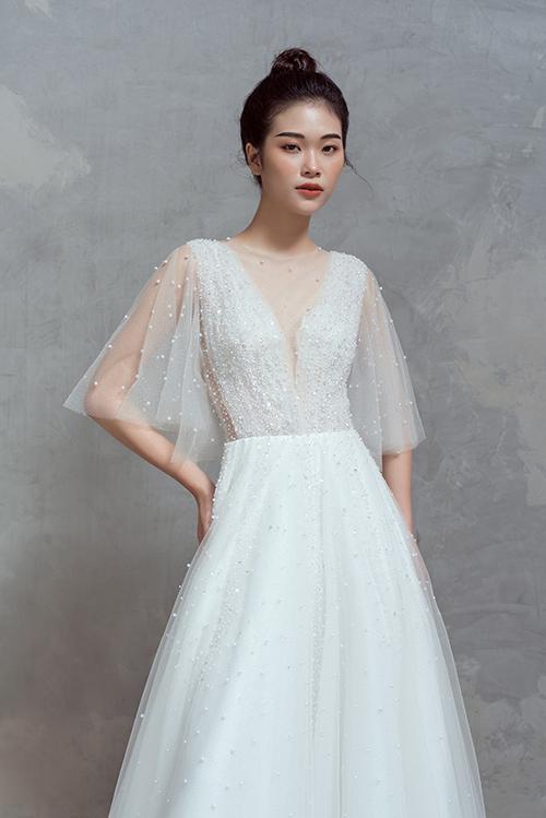 Váy cưới tay cánh tiên được tạo dựng từ nhiều lớp lang tạo sự dày dặn, phù hợp với tiết trời thu đông. Vì váy làm từ chất liệu cao cấp nên không gâycảm giác nặng nề, bức bí cho cô dâu khi diện.