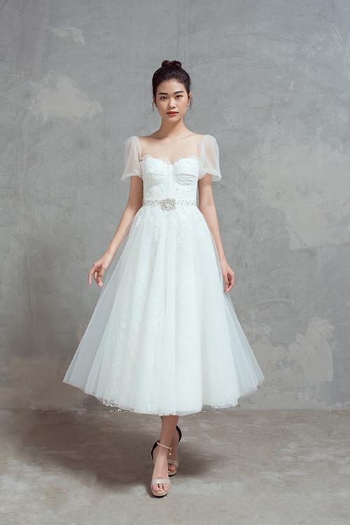 Váy cưới ngắn là một lựa chọn thú vị cho nàng dâu tổ chức tiệc cưới sân vườn, bãi biển. Bộ đầm được dựng gọng corset có tác dụng nâng đẩy vòng 1, có thiết kế tay bồng nhẹ nhàng.