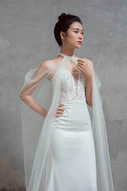 Bộ cánh biến hóa thành kiểu váy khác khi cô dâu kết hợp phụ kiện áo choàng voan mỏng.Bộ ảnh được thực hiện bởi làm tóc - trang điểm - trang phục: Thịnh Nguyễn Bridal, nhiếp ảnh: Du Miên, người mẫu: Uyên Đỗ