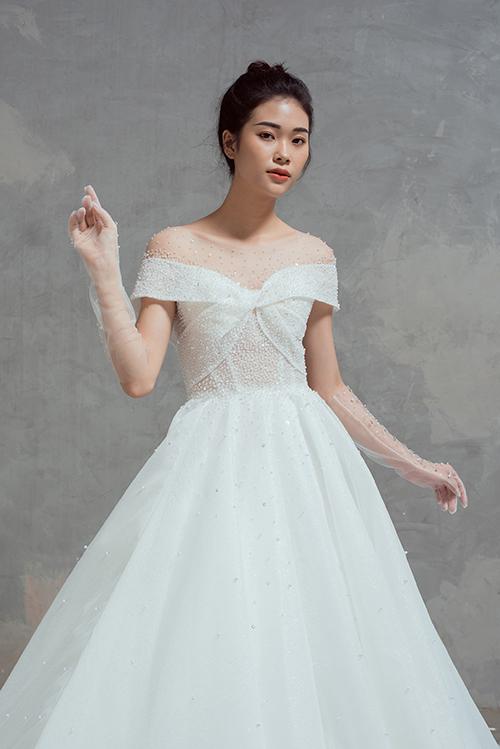 Giá trị thẩm mỹ của váy xòe bồng nằm ở thiết kế xoắn nơi ngực áo, cổ illusion từ voan mỏng điểm hạt pha lê.