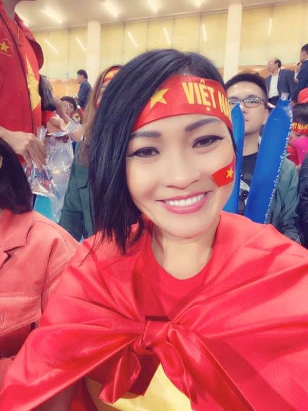 Phương Thanh đeo băng rôn, khoác quốc kỳ trên khán đài sân vận động Mỹ Đình. Chị bay từ TP HCM ra Hà Nội hôm 18/10 để theo dõi đội tuyển quốc gia thi đấu.