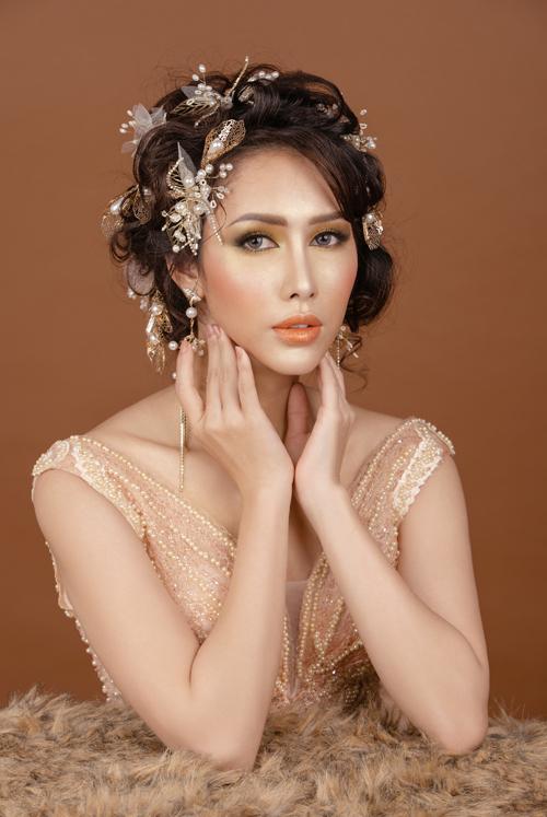 Đôi môi phủ tông vàng cam như sắc màu mật ong, hợp với làn dangười châu Á. Mái tóc được làm điệu với phụ kiện cài tóc hình cánh bướm hoặc cặp tóc ngọc trai, giúp gương mặt cô dâu thêm thu hút.