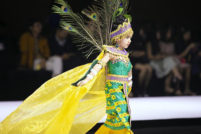 Trang phục lộng lẫy với sắc vàng hoàng kim rực rỡ giúp các bé nổi bật trên sân khấu thời trang.