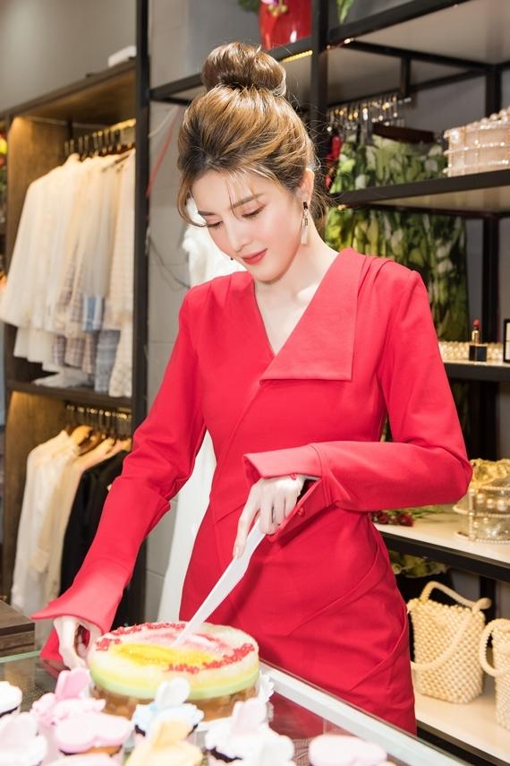 Người đẹp tự tay cắt bánh kem khai trương cửa hàng.