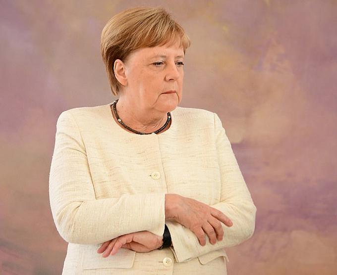 Bà Merkel ôm cánh tay run lẩy bẩy của mình hôm 27/6. Ảnh: EPA.