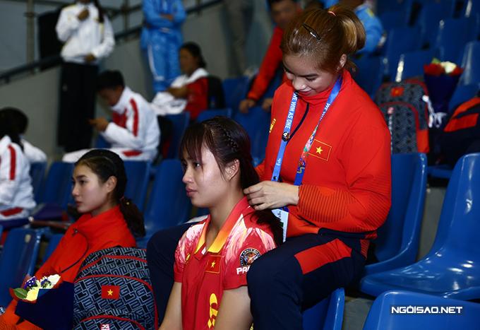 Võ sĩ Lê Thị Vân Anh nhờ đồng đội tết tóc trong thời gian chờ đợi ban tổ chức trao huy chương sau khi kết thúc ngày thi đấu 2/12.