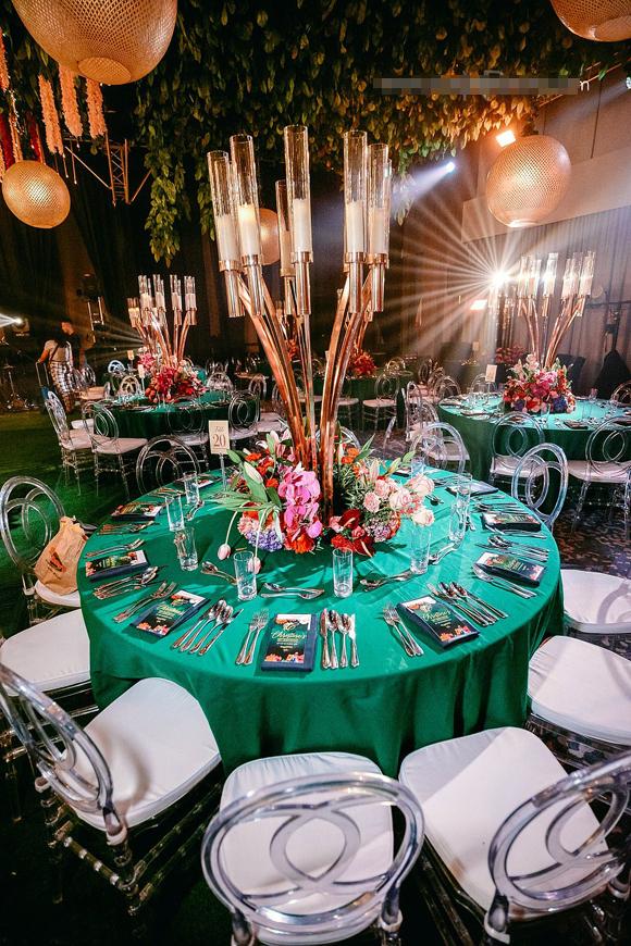 Khu vực tiệc được trang trí phía trên là đèn chùm, dàn hoa treo lộng lấy. Bàn tiệc đặt bộ dao dĩa bạc và phòng khiêu vũ giống như một phim trường.