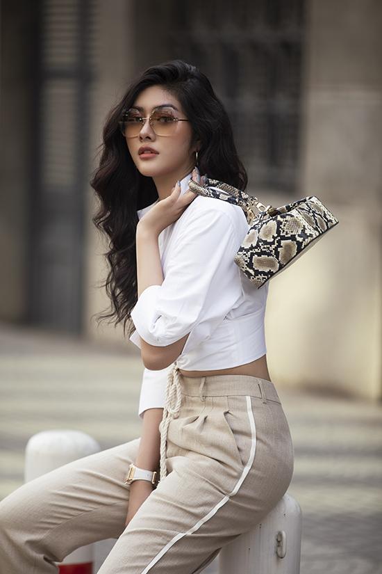 Túi xách tay kiểu dáng độc đáo, thiết kế trên chất liệu da trăn được hoa hậu chọn làm điểm nhấn cho set đồ đơn sắc.