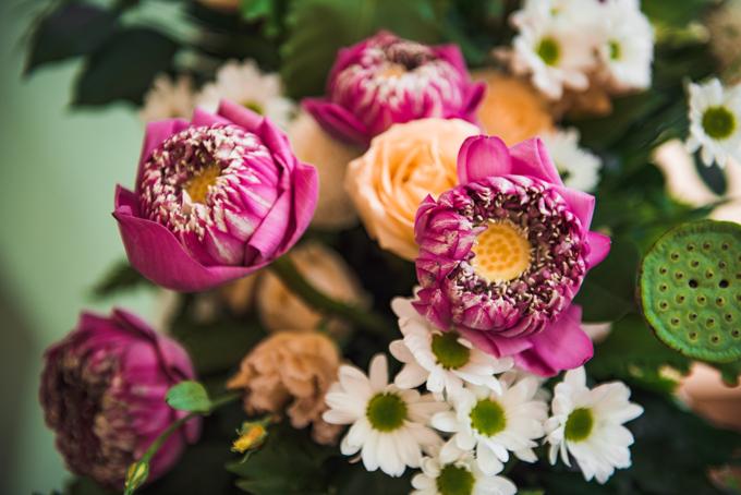 Cánh hoa sen được gập thành hình tam giác nhọn, tạo sự độc đáo, phối cùng một số loài hoa, lá tông trắng, cam, xanh lá để trang trí.