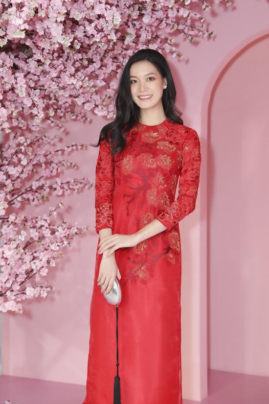 Hoa Hậu Thuỳ Dung chọn áo dài đỏ rực rỡ của nhà thiết kế Thủy Nguyễn để chưng diện. Trên gam tông màu được ưa chuộng trong dịp lễ Tết, trang phục truyền thống được tô điểm họa tiết hoa mẫu đơn ánh vàng.