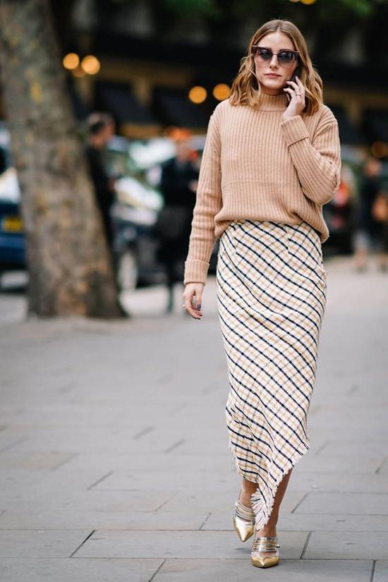 Giày ánh kim là phụ kiện tạo nên điểm nhấn cho set đồ gồm áo len màu trung tính phối cùng chân váy họa tiết